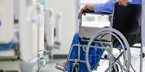 SCI-patient-in-wheelchair-being-pushed-by-nurse