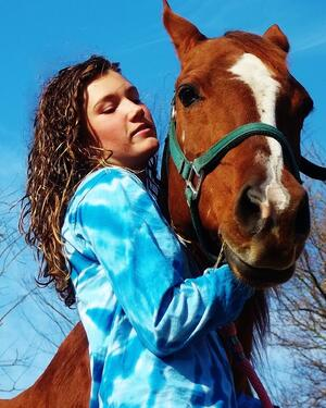 A photo of Carley Dole, a spinal cord injury survivor and TBI survivor, shares her insights in a blog post for Spinal Cord. The photo features her with a horse.
