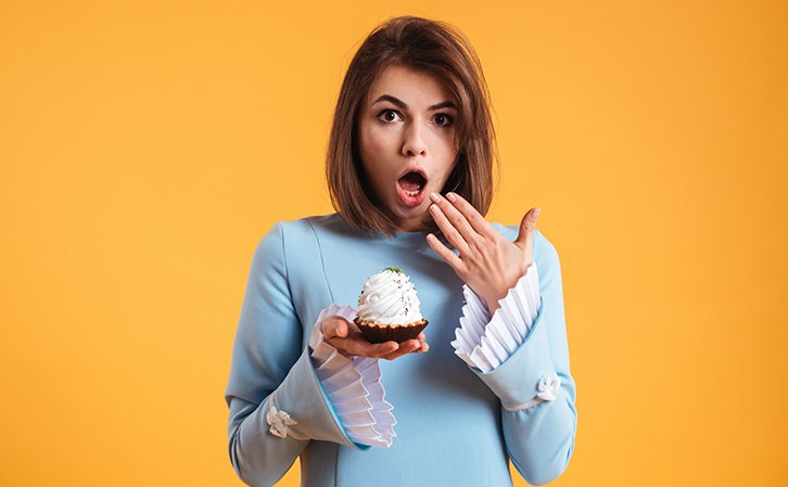 astonished young woman holding cake