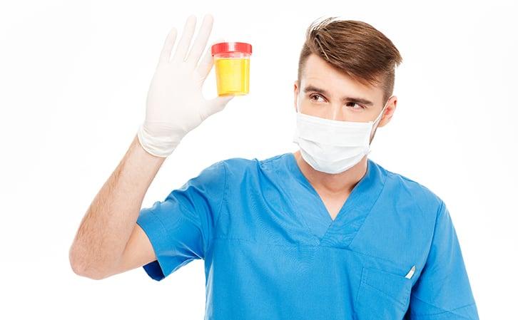 man holding urine sample for UTI