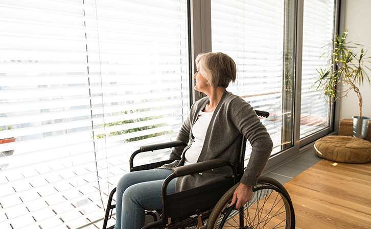 woman in wheelchair looking through blinds